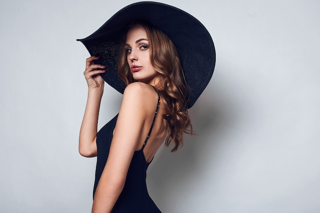 Elegant beautiful woman in a black dress and hat Premium Photo