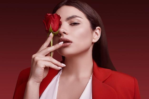 Элегантная красивая женщина в красном модном костюме с розой Premium Фотографии