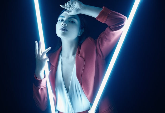 Elegant beautiful woman in a red fashionable suit posing with neon lights Premium Photo