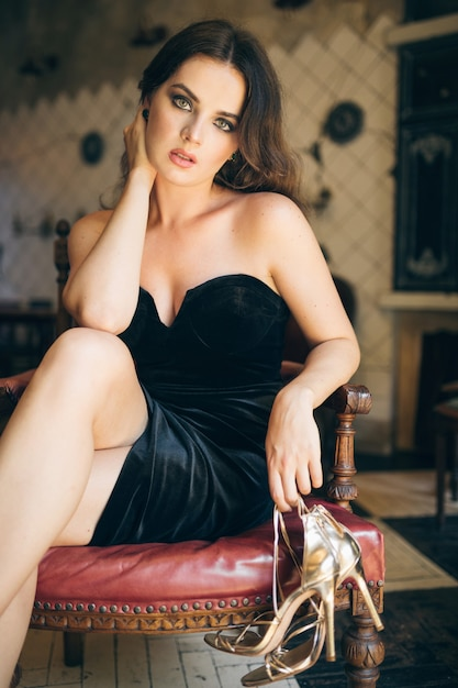 黒のベルベットのドレス、リッチでスタイリッシュな女性、エレガントなファッショントレンドでヴィンテージカフェに裸足で座っているエレガントな美しい女性は、彼女の靴、金色のハイヒールのサンダルの靴を脱いだ 無料写真