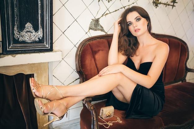 검은 벨벳 드레스, 이브닝 가운, 풍부한 세련된 아가씨, 우아한 패션 트렌드, 섹시한 매혹적인 외모, 매력적인 스키니 인물, 굽 신발을 신고 빈티지 카페에 앉아 우아한 아름다운 여인 무료 사진