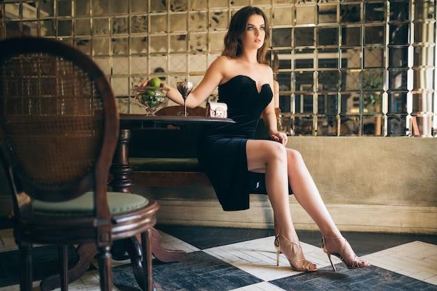 검은 벨벳 드레스, 이브닝 가운, 풍부한 세련된 숙녀, 우아한 패션 트렌드, 섹시한 매혹적인 외모, 발 뒤꿈치에 긴 다리가있는 매력적인 마른 체형의 빈티지 카페에 앉아있는 우아한 아름다운 여인 무료 사진