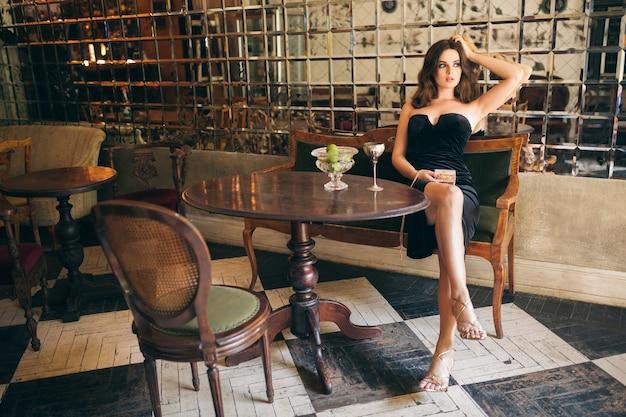 검은 벨벳 드레스, 이브닝 가운, 풍부한 세련된 여성, 우아한 패션 트렌드, 섹시한 매혹적인 외모, 매력적인 스키니 인물의 빈티지 카페에 앉아 우아한 아름다운 여인 무료 사진