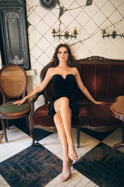 黒のベルベットのドレス、イブニングドレス、リッチでスタイリッシュな女性、エレガントなファッショントレンド、セクシーな魅惑的な外観、魅力的なスキニーフィギュアでヴィンテージカフェに座っているエレガントな美しい女性 無料写真