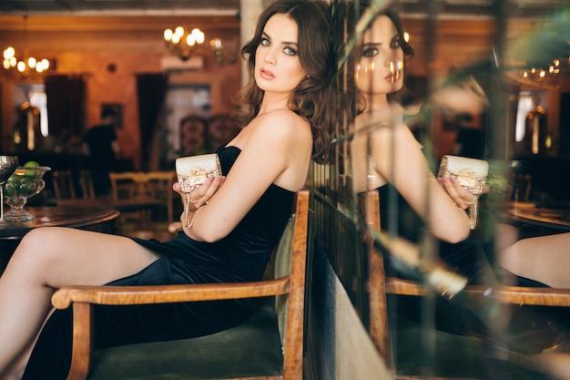검은 벨벳 드레스, 이브닝 가운, 풍부한 세련된 아가씨, 우아한 패션 트렌드, 날짜를 기다리고, 작은 황금 핸드백을 손에 들고 빈티지 카페에 앉아 우아한 아름다운 여인 무료 사진