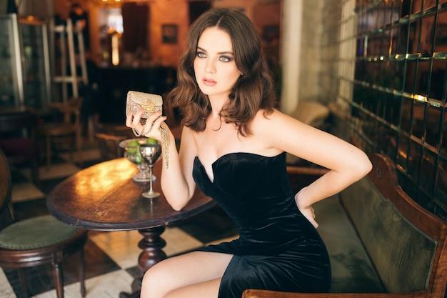 Elegante bella donna seduta nel caffè vintage in abito di velluto nero, abito da sera, ricca signora elegante, tendenza della moda elegante, sexy fiducioso, tenendo la borsa d'oro Foto Gratuite