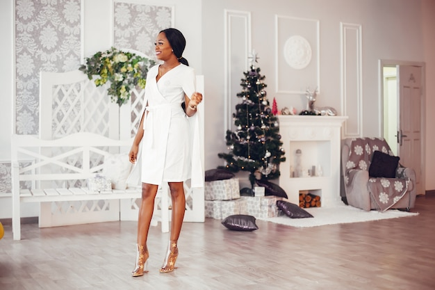 Elegant black girl in the christmas decorated room Free Photo
