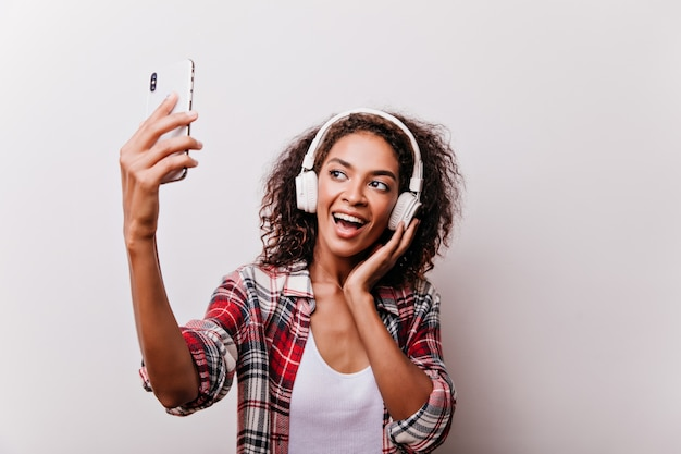 Elegant black girl listening music while taking picture of herself. enthusiastic woman using phone for selfie. Free Photo