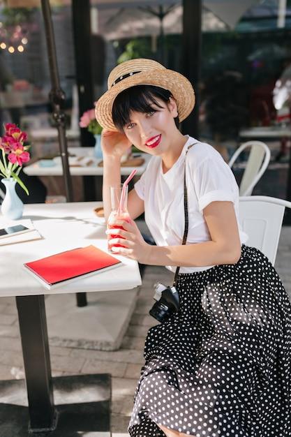 Elegante ragazza dai capelli neri in camicia bianca e gonna a pois che riposa nella caffetteria con un bicchiere di cocktail ghiacciato dopo il servizio fotografico Foto Gratuite
