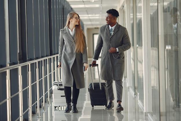 Elegante uomo di colore in aeroporto con il suo partner d'affari Foto Gratuite