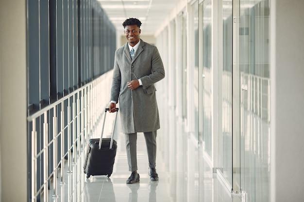 Elegante uomo di colore in aeroporto con una valigia Foto Gratuite
