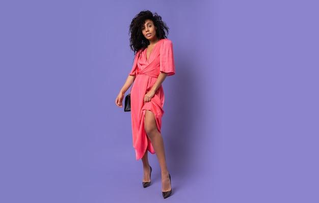 Elegante donna nera in abito da sera rosa in posa sopra la parete viola. indossare i tacchi. intera lunghezza. Foto Gratuite