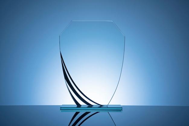 Elegant blank glass shield trophy on blue gradient Premium Photo