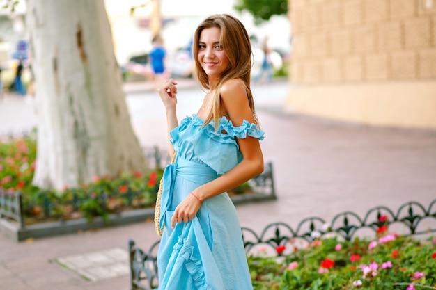 フェミニンなエレガントな青いドレスとストローバッグを着て、ヨーロッパの街を歩いてエレガントな至福の幸せな女 無料写真