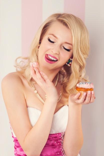 머핀에서 크림을 먹는 우아한 금발 여자 무료 사진