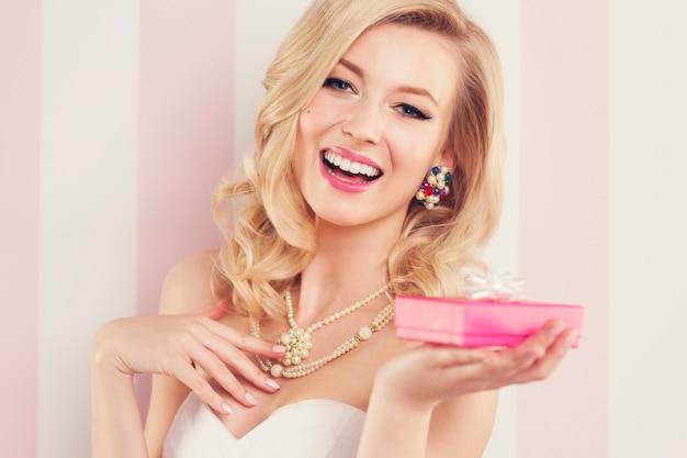 Elegante donna bionda che tiene un regalo rosa Foto Gratuite