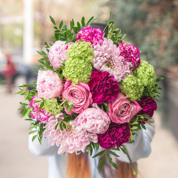 An elegant bouquet of pink and purple flowers with decorative green leaves Free Photo