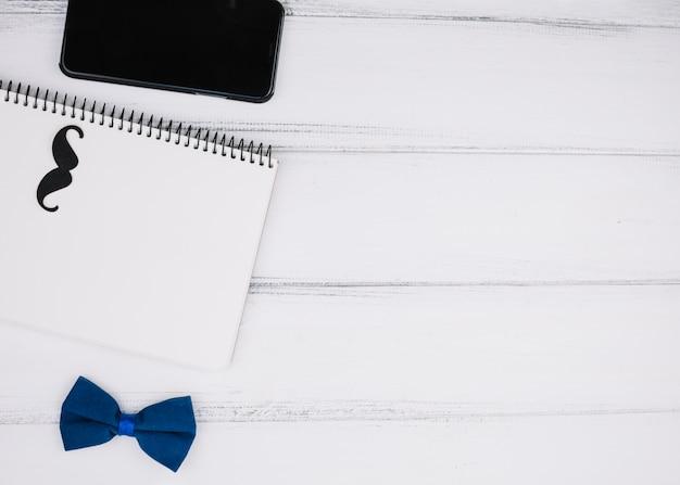Elegante papillon vicino a baffi di carta su notebook e smartphone Foto Gratuite