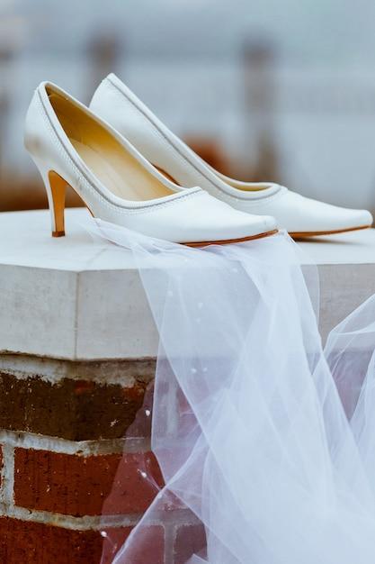 Elegant bridal shoes and white on the beach Premium Photo