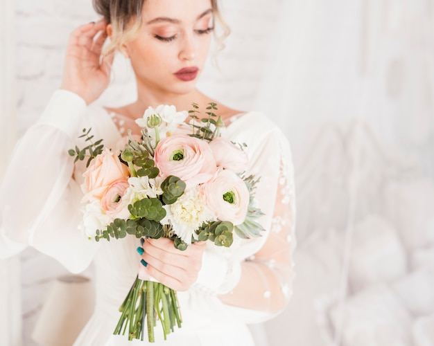 Elegant bride posing with her bouquet Free Photo