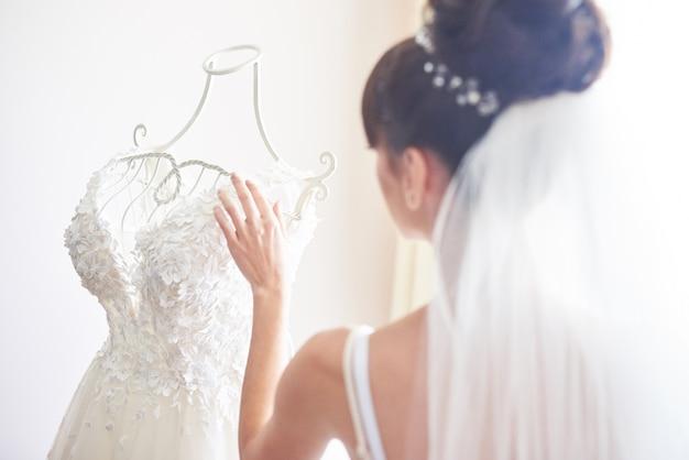 エレガントな花嫁は彼女の部屋にウェディングドレスを置きます。 無料写真
