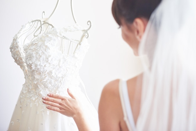 Elegant bride puts a wedding gown in her room. Free Photo