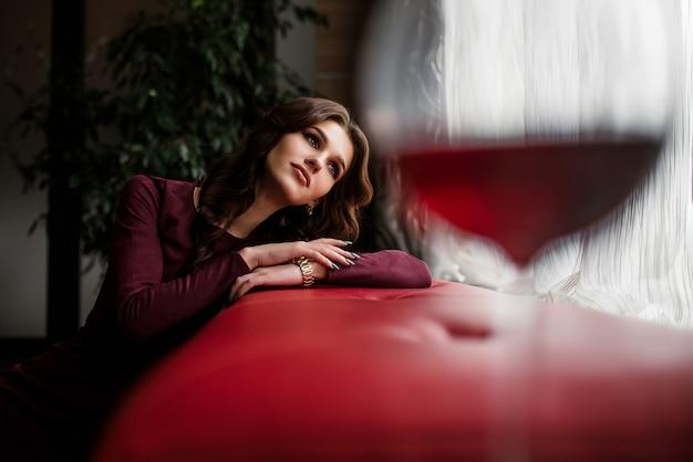 Элегантная дама брюнетка с бокалом красного вина в ресторане. Premium Фотографии