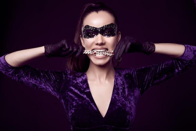 Elegante donna bruna in un bellissimo vestito viola, maschera di paillettes e guanti neri Foto Gratuite