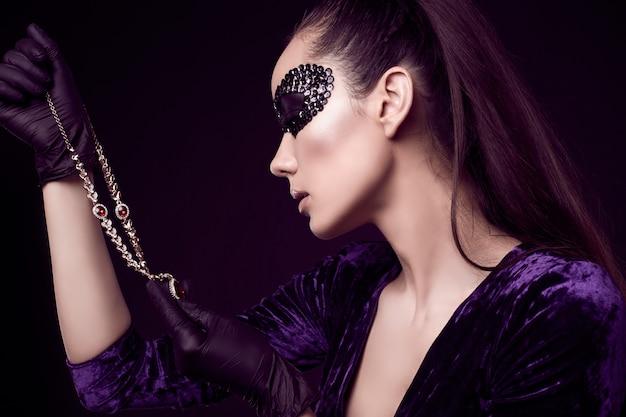 Elegante donna bruna in maschera di paillettes con guanti neri guarda la collana di diamanti Foto Gratuite