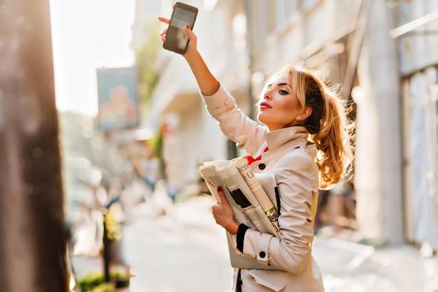 コートを着たエレガントなビジネス女性が晴れた日に働くために急いでタクシーを捕まえる 無料写真