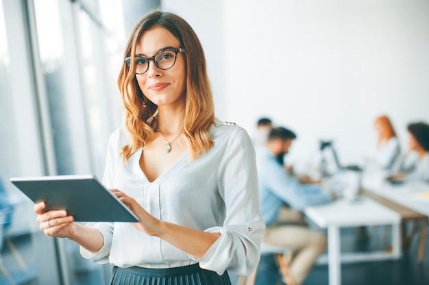Elegant businesswoman standing in office with digital tablet Premium Photo
