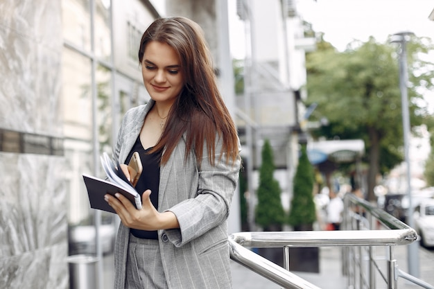 Elegant businesswoman working in a city and use the notebook Free Photo