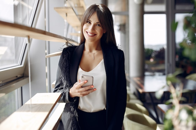 Elegant businesswoman working in a office and use the phone Free Photo