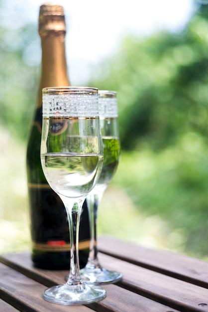 Элегантные бокалы для шампанского с бутылкой шампанского на деревянный стол Бесплатные Фотографии
