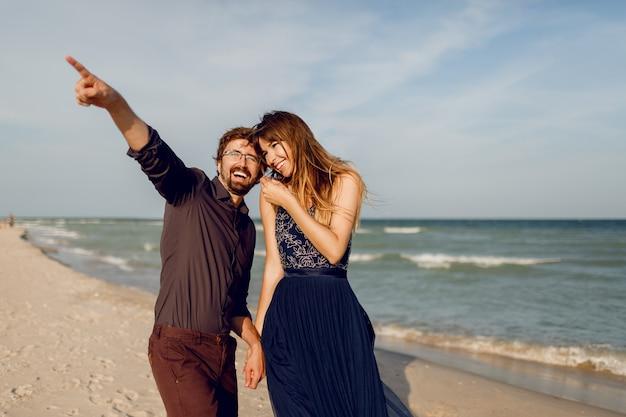 太陽が降り注ぐビーチの上を歩く愛のエレガントなカップル。ロマンスムード。スパンコール付きのエレガントな青いドレスを着ている女性。彼女の夫は何かを指しています。 無料写真