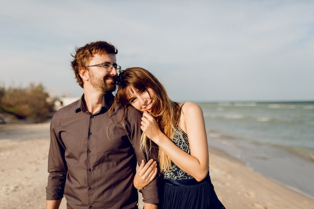 日当たりの良い夜のビーチ、夫を恥ずかしい幸せな女の上を歩く愛のエレガントなカップル。 無料写真