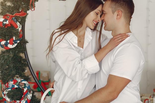 크리스마스 선물 근처 집에 앉아 우아한 커플 무료 사진