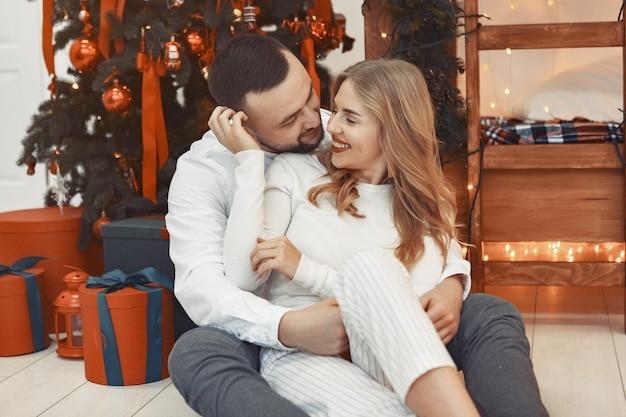 Элегантная пара сидит дома возле елки Бесплатные Фотографии