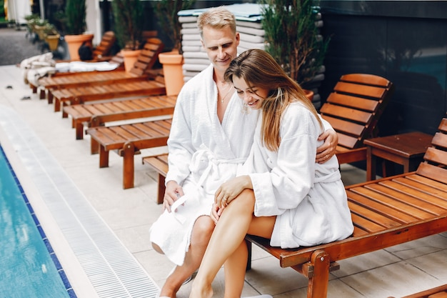 Elegant couple sitting near a swimmingpool Free Photo