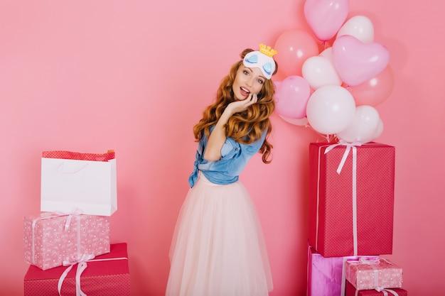 무성한 트렌디 한 스커트를 입은 우아한 곱슬 소녀는 친구들의 생일 선물 수에 놀랐습니다. 파티에서 선물과 헬륨 풍선과 함께 포즈를 취하는 수면 마스크에 매력적인 장발 젊은 여자 무료 사진