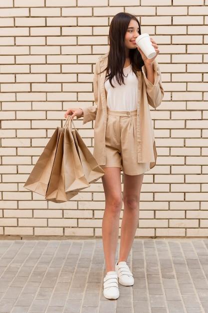 コーヒーを飲みながらバッグを保持しているエレガントな服を着た女性 無料写真