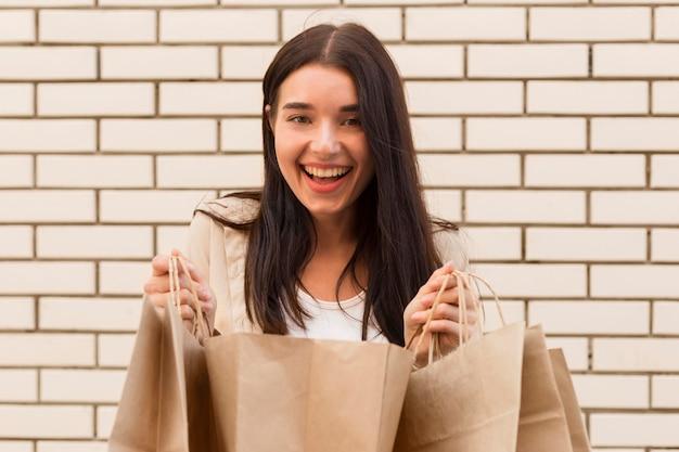 開いているショッピングバッグを保持しているエレガントな服を着た女性 無料写真