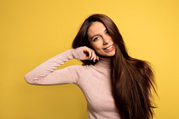 Элегантная европейская девушка с красивыми карими глазами трогает пальцами подбородок и нежно улыбается. макро портрет модной молодой женщины, позирующей в желтой комнате Бесплатные Фотографии