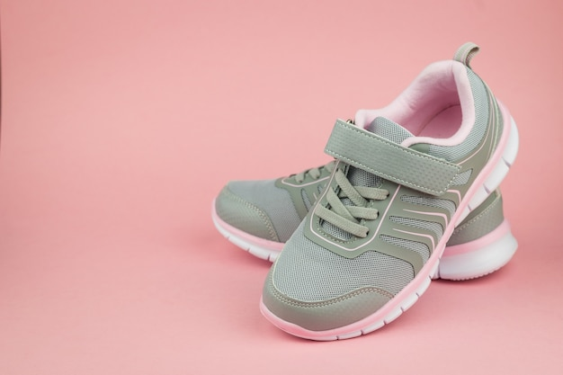Elegant fashion gray sneakers on pink background. sports shoes. color trend. Premium Photo