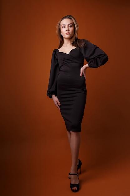 深いネックライン、ハイヒールの靴のポーズで黒のドレスのエレガントなファッションモデル。アジアの細い若い女性はセクシーなイブニングドレスに立っています Premium写真