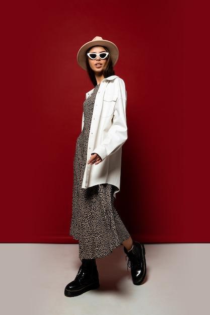 흰색 재킷과 드레스 포즈에 우아한 유행 여자. 블랙 가죽 앵클 부츠. 전체 길이. 무료 사진