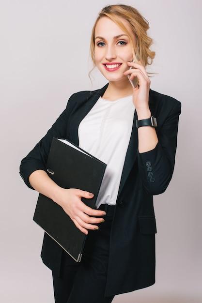 Elegancki, modny, młoda kobieta w biurze, trzymając folder, rozmawia przez telefon na białym tle.  Wesoły Nastrój, Sukces, Kariera, Zajęty, Pracujący, Prawdziwie Pozytywne Emocje Darmowe Zdjęcia