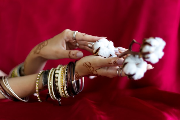 Elegant female wrists painted with traditional indian oriental mehndi ornaments by henna. hands dressed in bracelets and rings hold branch with cotton flowers. vinous fabric with folds on background. Premium Photo
