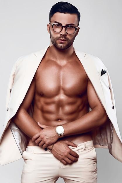 Elegant fit brutal man model in a light suit and glasses Premium Photo