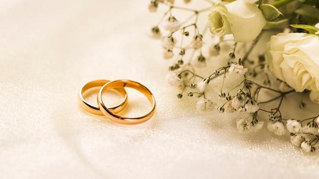 Bouquet di fiori eleganti e anelli di fidanzamento Foto Gratuite